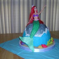 Mermaid Barbie's fish tail is made of gumpaste and fondant, making it appear that she sits on the cake. She is actually stuck into the center...