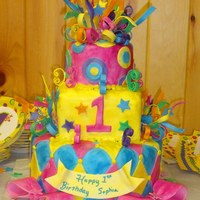 Whimsical Mardi Gras Themed Birthday Cake For First Birthday this Mardi Gras cake has 7 different colors to match child's birthday outfit. All streamers, bows, stars, ribbons are edible gumpaste...