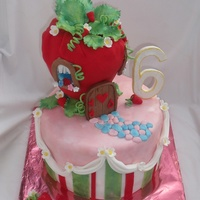 Strawberry Shortcake Theme House Cake strawberry house is red fondant covered rice krispy treats. All decorations are handmade, edible gumpaste or half gumpaste/half fondant.