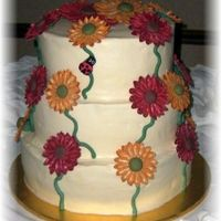 Fondant/gumpaste Gerbera Daisy Cake  I was so worried about how these flowers would attach to the cake. But it all turned out ok. EXCEPT....I only charged the bride $50 for the...