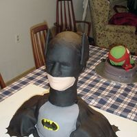 Batman Huge amount of chocolate cake with choc frosting all covered in fondant. Head is a male wig head also covered in fondant so it also serves...