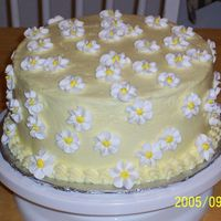 Sunshine And Daisies White Cake iced in buttercream. Flowers are royal icing. It's a variation on one of the cakes in Wilton Course 1