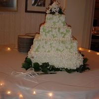 Green With Overlay Of White Flowers, All Buttercream Topper and base under cake, silk flowers (done by MOB)All decorating is buttercream, with edible pearl accents. This design would work with...