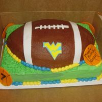 "Wvu Football Football pan on 9""x13"". Fondant WV, accents on football, and basketballs. Everything else is BC."