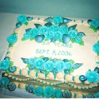 Blue Seashell Anniversary Cake   French Vanilla cake, buttercream frosting, white chocolate shells, dusted with blue luster dust