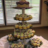 Cupcake Wedding Cake  Cupcake Wedding Cake done on a Wilton display. The display is edged in green leaves. Each cupcake had a hand made flower on it. The top...