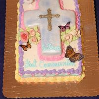 First Communion 1/2 sheet with cot out cross shape covered in fondant. Roses made from chocolate paste and butterflies are rice paper pre-printed.