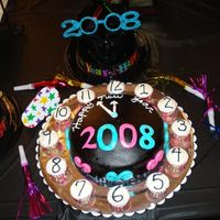 New Years Cake Black food colored marshmallow fondant covered french vanilla cake with mmf decorations. Mini cupcakes used for times and buttercup...