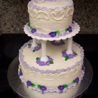 Purple Violet Wedding Cake Top layer is white cake with lemon filling, bottom cake is red velvet with cream cheese filling. Both are covered with buttercream frosting...