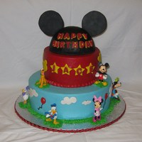Mickey Mouse Cake Buttercream with fondant decorations. Chocolate letters. RKT hat with gumpaste ears. the figures are toys.