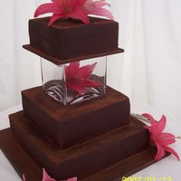 Chocolate Lily Chocolate cake finished with ganache. The top tier is separated with a vase and fresh flowers for decoration.