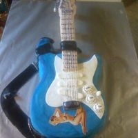 Fender Strat Guitar  This was a replica of a fender strat guitar. Base is cake and neck is rice krispie treats. Decorated all with fondant except guitar strings...