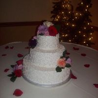 Sand Colored Scroll Work round stacked cakes with sand colored scrollwork and fresh flowers.