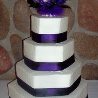 Hex Shape   plain iced buttercream hex cakes with satin purple ribbon and fresh flower topper.