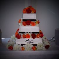 Danielle's Cake This is a three tiered square cake. It is iced in BC with brown ribbon around the bottom of each tier. The flowers are real roses and silk...