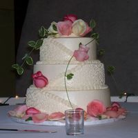 Gina's Cake This is a three tiered French Vanilla cake. It is iced in BC, 1/2 cornelli lace design , with fresh roses and ivy. It was inspired by a...