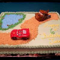 Cars Cake This is a full sheet cake iced in BC. The road is made with smashed up graham crackers.