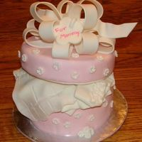 "Pretty Present MMF covered 6"" cake. Fondant covered 6"" styrofoam lid. Fondant embossed flowers, handmade fondant bow and baby clothes."