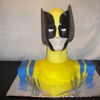 Wolverine Cake shoulders covered with fondant. Wolverine's head is a man's styrofoam head painted with glow in the dark paint and sheet...