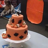 Halloween 2 tiered cake with pumpkins, bats, ghosts, skulls,bones and a witch's head on top.