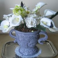 Flower Pot ,urn :orchids,roses,dogwood,lillies,green Leaves,edible Butterflies flowers out of gumpaste and urn is white vanilla with swiss meringue and caramel filling, wrapped with satin ice fondant.