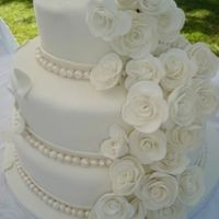 White Wedding Cake Three tiered wedding cake, covered in fondant. Roses and pearls are handmade from fondant and dusted with pearl luster dust. Imade this for...