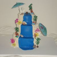 Laua Cake  This was a fun cake to make with a fondant waterfall and white buttercream beach. Gumpaste flowers and plastic hawaiian hula dancers and...