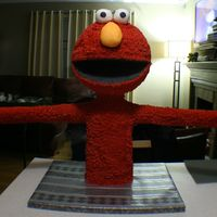 Elmo Serves Up Cake  He stands about thirty inches tall and his hands were about four feet apart at the cakes. his head was made with a ten inch, three layer...