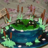 Picture_014_2.jpg Chocolate cake covered in fondant,airbrushed in blue with darker blue brushed on.Frogs,dragonflies,water lilies,& sign made of gum...