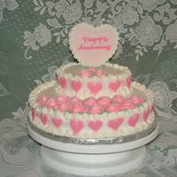 Dscf0015.jpg  Yellow cake covered in rolled butter cream.Roses & border are piped butter cream.Hearts are royal icing run outs.Center heart is gum...