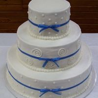 Round Wedding Cake 14,10,& 6 in round stacked cake. All buttercream with blue ribbons.