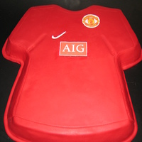 Mancherster United Football / Soccer Jersey / Top Chocolate cake carved to shape and covered in ganache and red fondant. Edible image logos. Made for a 40th birthday for a guy who LOVES...