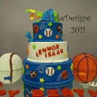 "1St Birthday Sports 5"", 7"" & 9"" stacked. 2 half balls. Iced in buttercream with fondant decorations."