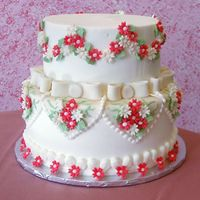 "Red & White Wedding Cake This was a last minute order for a small Wedding Cake. Iced in Buttercream Icing w/ Red & White fondant flowers. Fondant hearts ""..."