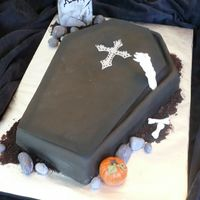 Coffin Cake Single layer sheet cake, cut in the shape of a coffin. Covered in fondant (black and chocolate combined), and all the accent pieces are...
