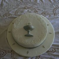 First Communion this cake, and base are covered in fondant. The chalice and host are also made with fondant and painted in luster dust. the small crosses...