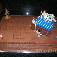 Toy Story I made this cake to look like Andy's bedroom with a lot of the characters all around the bed. The bed is a cake also with Hershey bars...