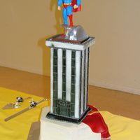 "Superman Groom's Cake The cake is a 12"" hex in red velvet with cream cheese icing. The building is cut from 1/2"" thick foam core, covered in fondant ,..."