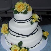 Black Stripe covered in fondand with fondant stipes and silk flowers.