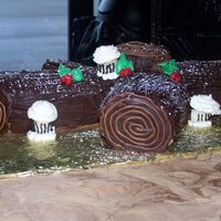 Yule Log yule log cake with yellow roulade, chocolate buttercream, and chocolate ganache.