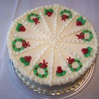 Christmas Cake Divided into pieces and decorated with holly leaves and wreaths. This cake is red velvet with vanilla buttercream