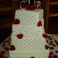 Square Wedding 8, 10, 12, 14 in square covered in fondant with buttercream accents. Black beads and fondant pearls. Red rose petals.