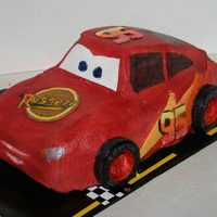 Lihtging Mcqueen Sculped and air brushed car, hand painted windows and logo, windshield is fondant. Rolled together yellow,red and orange fondant to make...