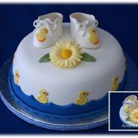 Just Ducky Baby Shower Handmade gumpaste booties and a gumpaste daisy adorn the top of this ducky - themed baby shower cake. The cake is covered in fondant, with...