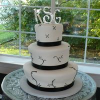 Very Elegant this is my drummer's wifes cake. Very simple but the whimsical shape to it represented her very fun personality! She was a great bride...