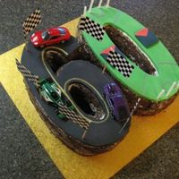 60Th Birthday Race Car Afl Footy Cake Chocolate mud cake, covered in buttercream and chocolate sprinkles. Fondant for the racing track and footy oval.