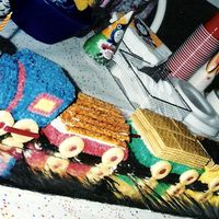 Train Lover's 1St Birthday  3D Train made 6 feet long. Cookies for wheels, licorice for wheel links. 1 train car with pretzel logs, 1 train car with graham cracker...