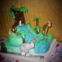 1St Try At A Jungle Theme Animals are molded in chocolate, large tree and rocks are candy clay, small trees are cookies covered in chocolate. Rest is buttercream.