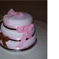 Pink And Brown Wedding 3 stacked round tiers of almond, chocolate and yellow cake with strawberry filling. Ribbon adornment and fondant bows.