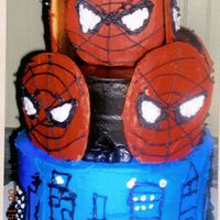 Spiderman Cake 1st tier white cake with strawberry jello, top is choc cake with choc frosting, spiderman faces on top are sugar cookies on a stick, th...